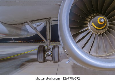 Close-up view on Airbus A320-232 aircraft's IAE V2500 engine, fuselage and left main landing gear at night. Tbilisi International Airport, Tbilisi, Georgia