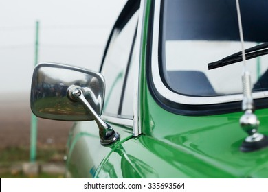 Closeup view on a chrome mirror of a classic car