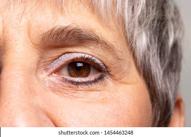 A closeup view on the eye of an old-aged woman waring blue eye shadow and eyeliner. Lady with brown eyes and grey hair with wrinkled face.