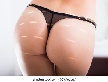 Close-up view on female buttocks in lace bikini underwear in sunlight
