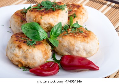 Closeup view on fried meatballs of minced chicken with red pepper and green basil on a striped background