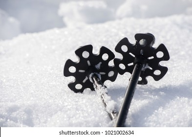 Closeup view on the lower part of the ski poles in the snow.