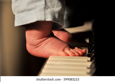 Closeup view on male babyboy bare feet with small toys playing on piano forte key board musical instrument with warm light indoor, horizontal picture