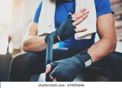 Closeup view on male hands of young athlete tying black boxing bandages.Boxer man relaxing after hard kickboxing training session in gym. Blurred background. Horizontal