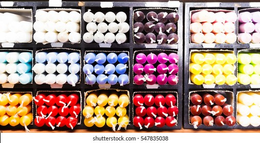 closeup view on multicolored candles sorted by color on shelf in store
