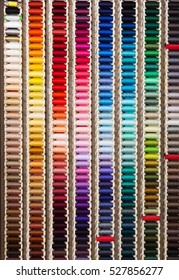 closeup view on multicolored stitching spools in sewing shop