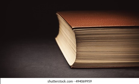Closeup view on an old closed book, details of paper and leatherette cover.