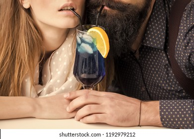 Closeup view on one attractive stylish emotional couple of young woman and senior man with long black beard drinking blue cocktail in glass with straw and orange slice intdoor, horizontal photo