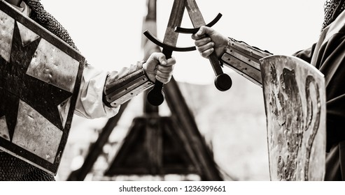 Closeup view on traditional medieval knights with shields and swords. Image in black and white color style