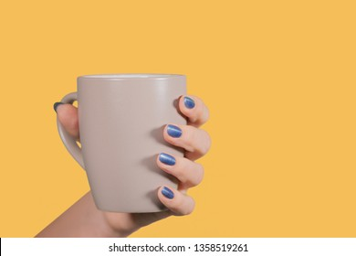 Closeup view of one beautiful female hand with painted blue glossy nails. Woman holding mug isolated on orange background. Horizontal color photography.