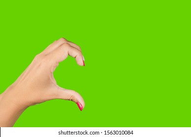 Closeup view of one beautiful female hand with perfect bright pink manicure forming half heart gesture with single hand isolated on bright chroma key green screen background with copyspace.