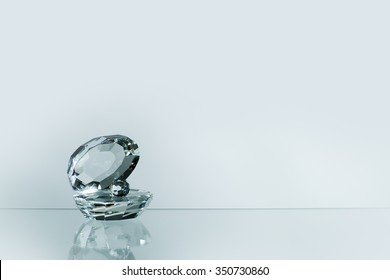 Closeup view of one beautiful luxurious magic fragrant transparent glassy faceted gem shell with precious pearl standing on reflecting table top in studio on grey background copy space, horizontal