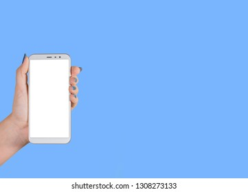 Closeup view of one female hand holding white modern smartphone with blank white screen isolated on blue background. Fingernails with modern glossy blue manicure. Horizontal color photography.
