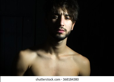 Closeup view of one handsome sexual sad pensive sensual young muscular man with brunette hair and beard and bare chest standing indoor looking forward on dark background, horizontal picture