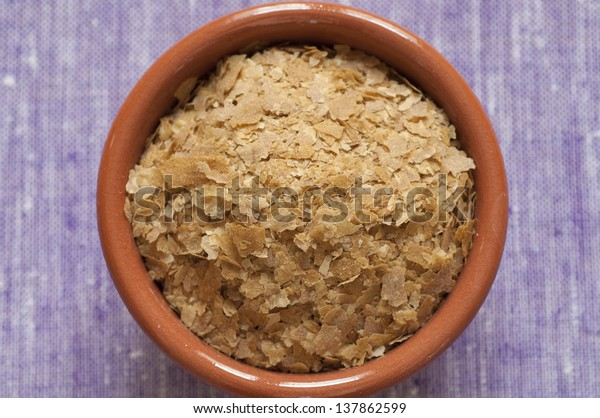 Close-up view of organic nutritional yeast flakes in a bowl