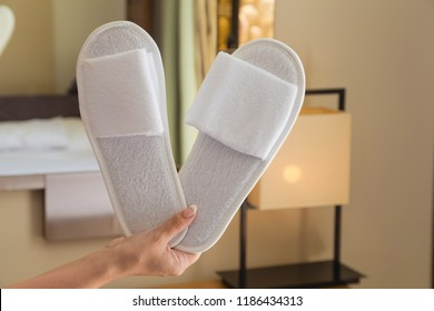 Closeup view of pair of white new slippers in hand of young woman at room of hotel interior background. Horizontal color photography.