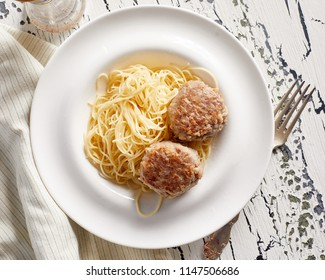 Close-up view of pasta with two cutlets on rustic white table