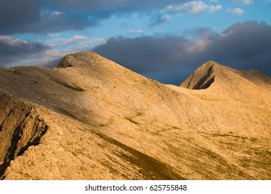 Closeup view of peaks Kutelo and Banski suhodol joined by the Koncheto Saddle in Pirin mountains under a stormy cloudy sky with a shaft of sunlight illuminating the range, Bulgaria