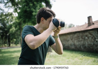 Close-up view of photographer looking through camera viewfinder. Portrait of man holding DSLR camera and looking through camera viewfinder.