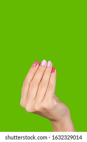 Closeup view photography of one beautiful manicured female hand isolated on green bright background. Woman making gesture as if holding something invisible with fingers.