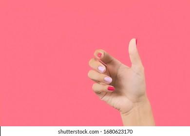 Nahaufnahme einer handgemachten, schönen weiblichen Hand, die Geste mit leerer Hand macht, als ob sie unsichtbares Objekt in einer Palme hält, einzeln auf hellrosa Hintergrund.