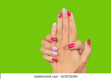 Closeup view photography of two beautiful manicured female hands isolated on green background. Woman showing her fresh stylish professional asymmetric colourful naildesign of fingernails.