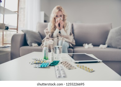 Close-up view of pile medicine colorful pills c-vitamin health support blonde girl suffering from allergy sitting on divan in light room