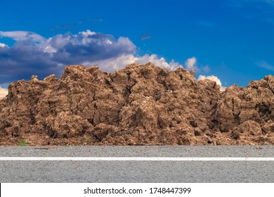 Close-up view of a pile of soil that has been dug on the side of the road with clouds and the sky as the daytime background in the Thai countryside.