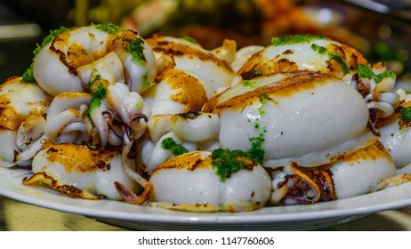 Close-up view of Plate of Grilled small Cuttlefish (squid) with garlic, olive oil and parsley