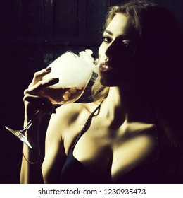 Closeup view portrait of one beautiful young sensual serious enigmatic enchanted woman holding in hand drinking glass full of liquid with smoke of magic elixir of beuty and life and secret of youth.