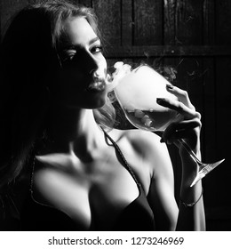 Closeup view portrait of one beautiful young sensual serious enigmatic enchanted woman holding in hand drinking glass full of liquid with smoke of magic elixir of beuty and life and secret of youth