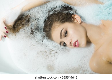 Closeup view portrait of one beautiful sensual attractive young woman with wet hair and bright makeup lying in bath tub with water and white soap foam looking away, horizontal picture