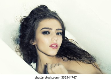 Closeup view portrait of one beautiful sensual pensive dreaming young woman with wet hair and bright makeup lying in bath tub with water and white soap foam looking forward, horizontal picture
