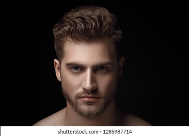 Closeup view portrait of one handsome bearded young macho man with strong look hazel eyes and sexy lips standing in light looking forward in studio on black background
