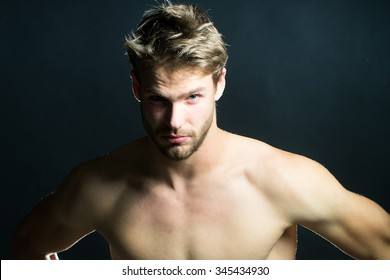 Closeup view portrait of one handsome young muscular naked sexy macho man with short hair bare chest and beautiful body standing in studio on black backdrop, horizontal picture