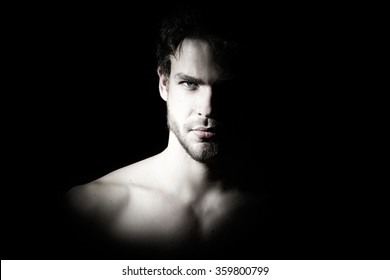 Closeup view portrait of one handsome bearded young macho man with strong look hazel eyes and sexy lips standing in light looking forward in studio on black background, horizontal picture