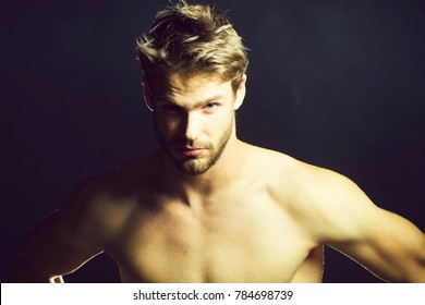 Closeup view portrait of one handsome young muscular naked sexy macho man with short hair bare chest abd beautiful body standing in studio on black backdrop, horizontal picture