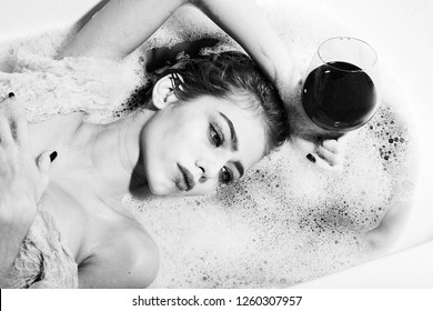 Closeup view portrat of attractive young sexy girl with wet hair lying in white bath tab full of water and soap foam holding drinking glass with red liquid as elixir of beauty or desert wine indoor.