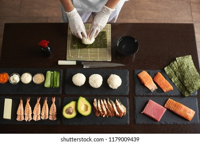 Close-up view of process of preparing rolling sushi. Nori and white rice. Chef's hands touch rice. Chef starts cooking sushi
