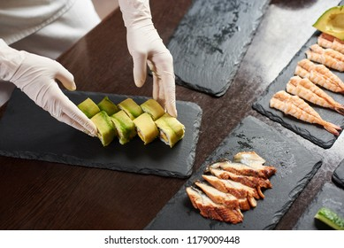 Closeup view of process of preparing rolling sushi. Master is serving fresh delicious rolls on the black stone plate