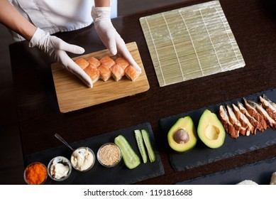 Closeup view of process of preparing rolling sushi. Master is serving fresh delicious rolls on the wooden board