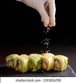 Close-up view of process of preparing rolling sushi. Hand in glove decorates delicious fresh rolls with a sesame. Dark background