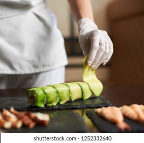 Close-up view of process of preparing rolling sushi at. Hand in glove decorates roll with sliced avocado