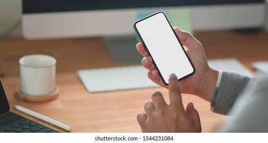 Nahaufnahme eines professionellen Geschäftsmanns, der sein leeres BildschirmSmartphone während der Arbeit an seinem Projekt anschaut