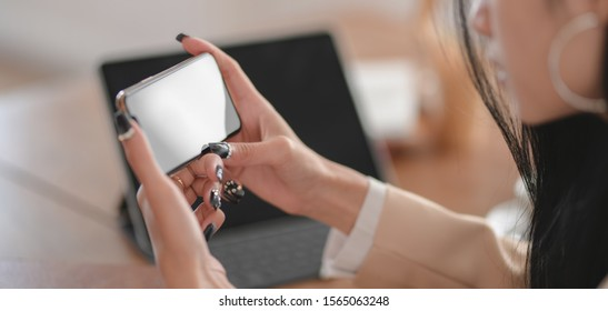 Close-up view of professional businesswoman working on her current project while looking for information in smartphone