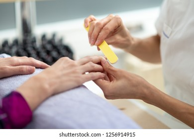Closeup view of professional manicurist shaping the nails with a file.