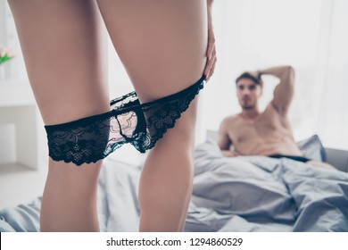 Close-up view of put off black small panties lady's legs in front of attractive handsome sporty muscular guy cheat affair pleasure safe sex life in light white interior indoors