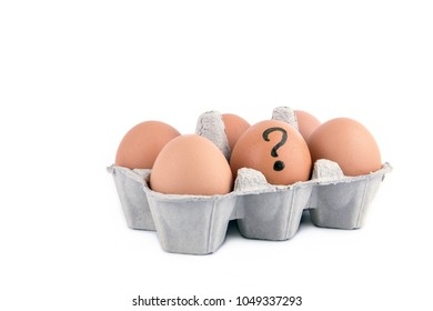 Close-up view of raw chicken eggs with question mark in box on white background