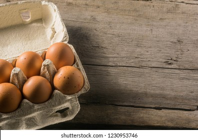 Close-up view of raw chicken eggs in egg box on black wooden background