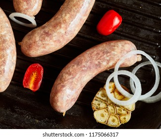 Close-up view of raw pork sausages on grill pan